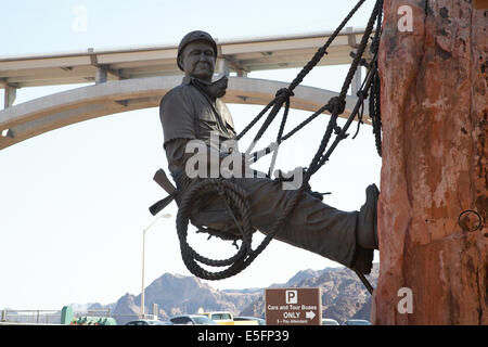 Statue of dam worker hanging on cliff at Hoover Dam, Nevada with the Mike O'Callaghan-Pat Tillman Memorial Bridge - Stock Photo