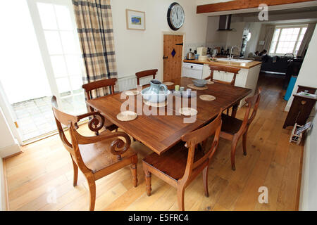 wooden table and chairs in a traditional cottage dining room. - Stock Photo