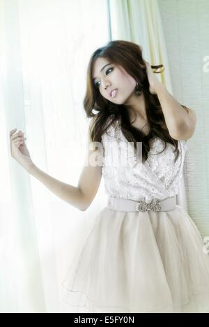 A beautiful young Asian woman dressed in white - Stock Photo