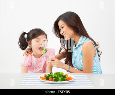 Young asian chinese mother feeding daughter - Stock Photo