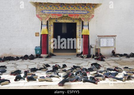 Monks took their shoes off before entering the prayer hall in the Labrang monastery - Stock Photo