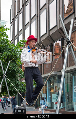 Street busker playing a violin while performing on a trapeze, Buchanan Street, Glasgow, UK - Stock Photo