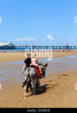 Young girl on a donkey ride with North Pier behind, The Golden Mile, Blackpool, Lancashire, UK - Stock Photo