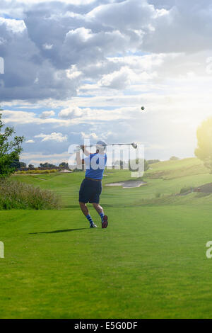 Male golf player teeing off golf ball from tee box in the sunset - Stock Photo