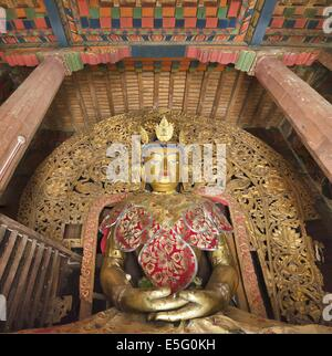 Sitting Buddha statue in the Gyantse Kumbum, a multi-storied aggregate of Buddhist chapels, in Tibet - Stock Photo