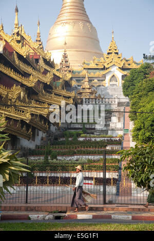 A street cleaner walks near one of the four grand covered stairways approaching the Shwedagon Pagoda in Yangon, - Stock Photo