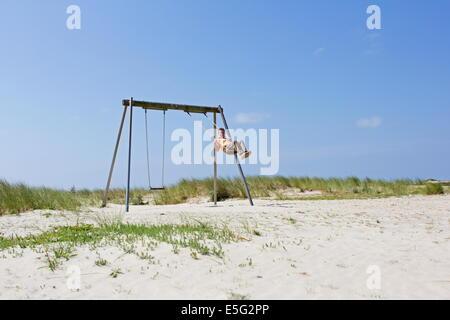 Borkum, Germany: July 29, 2014 - lady rocking on the playground - Stock Photo