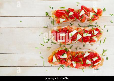 Ready to eat italian bruschetta with tomatoes and rosemary - Stock Photo