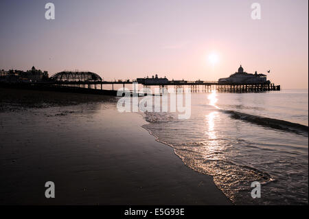 Eastbourne, Sussex, UK. 31st July, 2014.  The sun rises over the tangled wreck of Eastbourne Pier this morning the - Stock Photo