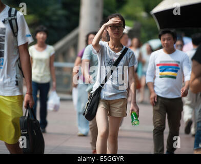 (140731) -- CHONGQING, July 31, 2014 (Xinhua) -- A pedestrian uses her hand to shelter from sunshine in downtown - Stock Photo