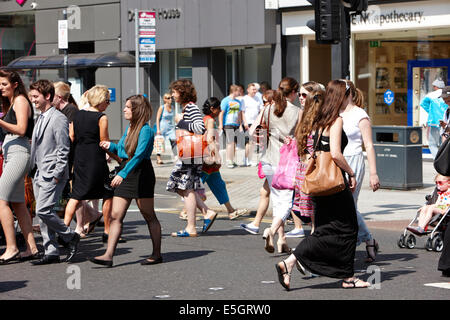 people crossing the road on a pedestrian crossing at lunchtime on busy summers day Belfast city centre - Stock Photo