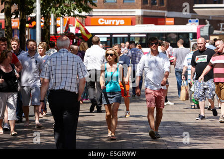people walking through busy cornmarket on a hot sunny day in Belfast city centre - Stock Photo