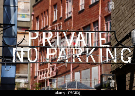 private no parking sign wrapped in barbed wire in a city centre in the uk - Stock Photo