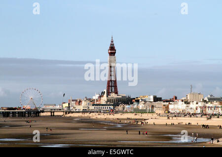 People on the beach at Blackpool with the tower and central pier in the distance - Stock Photo