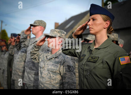 U.S. Airmen salute as the national anthems of the U.S. and France are played during a ceremony in the town of Picauville, - Stock Photo