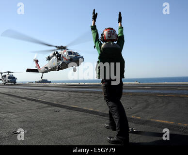 U.S. Navy Aviation Electronics Technician 3rd Class Elizabeth McKinney directs an MH-60R Seahawk helicopter assigned - Stock Photo