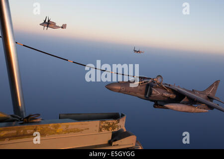 A U.S. Marine Corps AV-8B Harrier II aircraft, right, assigned to the 22nd Marine Expeditionary Unit (MEU) refuels - Stock Photo