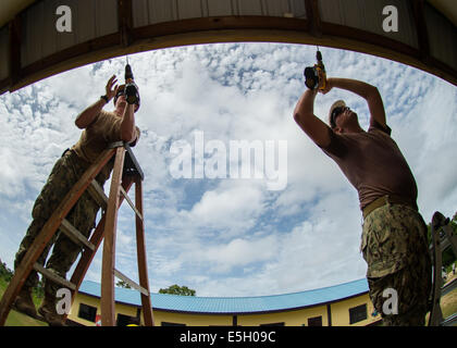 U.S. Navy Builder 3rd Class Matthew Wyatt and Engineering Aide 3rd Class Christopher Ardell perform renovations - Stock Photo