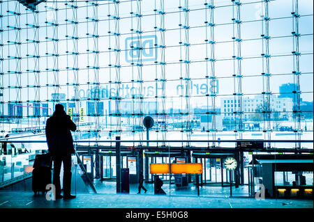Businessman in silhouette with luggage, making call on mobile phone in Berlin main  railway station. - Stock Photo