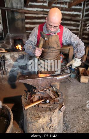 Blacksmith hammering on anvil, Festival du Voyageur, Winnipeg, Manitoba, Canada - Stock Photo