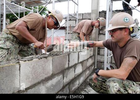 U.S. Navy Equipment Operator 3rd Class Eduardo Ellorin, left, and Steelworker Constructionman Cory Migneault spread - Stock Photo