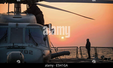 U.S. Sailors conduct post-flight maintenance on an MH-60R Seahawk helicopter assigned Helicopter Maritime Strike - Stock Photo