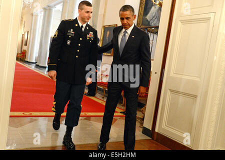 President Barack Obama, right, and U.S. Army Staff Sgt. Ryan Pitts enter the East Room of the White House in Washington, - Stock Photo