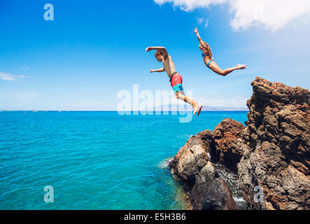 Friends cliff jumping into the ocean, summer fun lifestyle. - Stock Photo