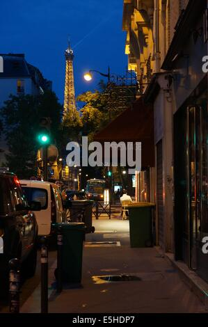 Paris street by night, cheese shop fromage one side, rear view of cars in front other side, with Eiffel tower lit - Stock Photo