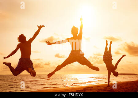 young people jumping on the beach with sunset background - Stock Photo