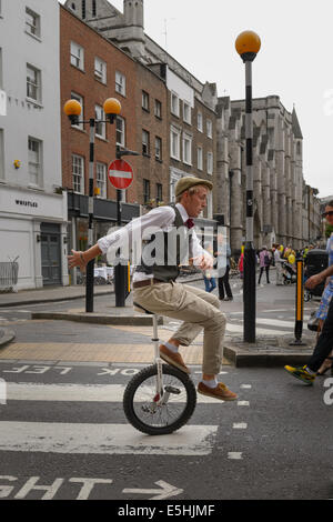 A street performer on a unicycle entertaining the public at Marylebone Street Summer Fayre fair, London, UK. - Stock Photo