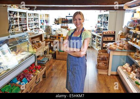 Owner Of Delicatessen Standing In Shop - Stock Photo