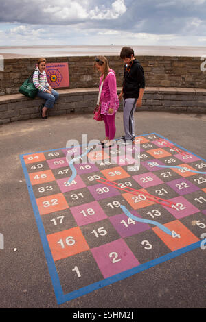 UK, England, Lincolnshire, Cleethorpes, seafront, children with mother playing game of giant snakes and ladders - Stock Photo