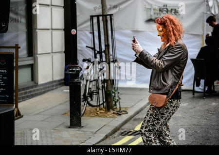 A young redhead woman takes a cellphone photograph on the street at Marylebone Street Fayre fair party, London, - Stock Photo