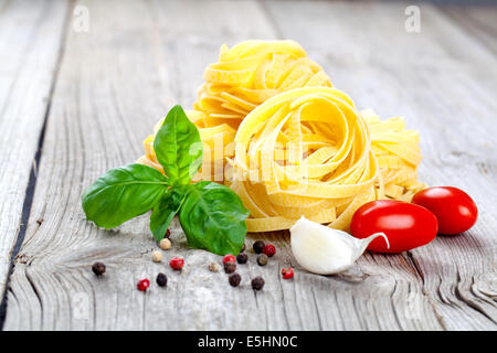Italian pasta fettuccine nest with garlic, tomatoes and fresh basil leaves, on wooden background - Stock Photo