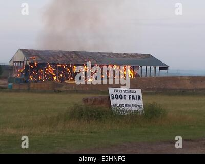 Isle of Sheppey, Kent, UK. 1st Aug, 2014. Huge fire breaks out at the newly built hay barn storage unit. Credit: - Stock Photo