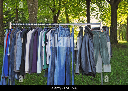 old, worn clothes on a hanging rail in a second hand market, outdoors, close up - Stock Photo