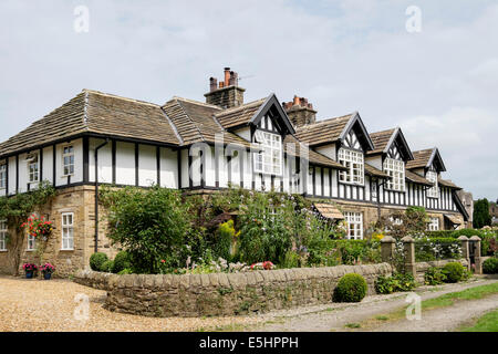 Row of 19th century Tudor style terraced houses (1882) with cottage gardens in summer. Whalley, Lancashire, England, - Stock Photo