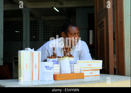 Man selling authentic Cuban cigars and cigarettes in shop - Stock Photo