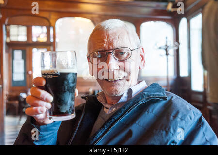 Elderly man drinking pint of Guinness in a pub, UK - Stock Photo