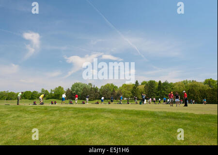 Golfers practicing their swing on a driving range. - Stock Photo