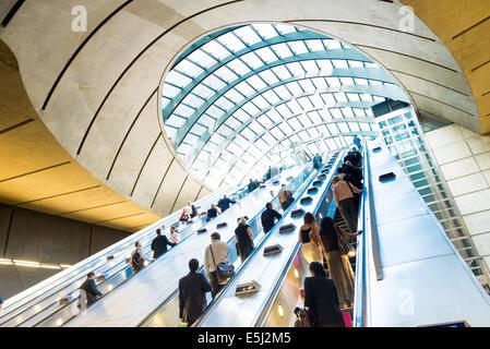 Up escalators at Canary Wharf underground station, London, England, UK - Stock Photo