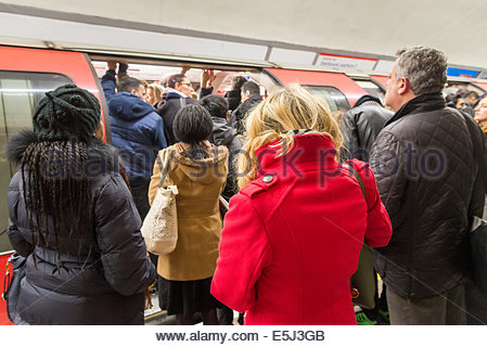 Commuters trying to board overcrowded Central Line London Underground carriage during the morning rush hour, England, - Stock Photo