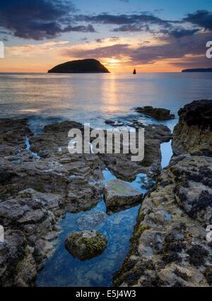 Trwyn Du lighthouse and puffin island at sunrise. - Stock Photo