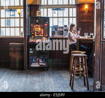 'The Market Porter' interior - inside a traditional London pub with gaming machine and woman sitting on barstool - Stock Photo