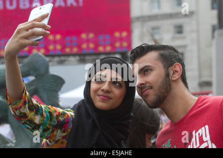 London,UK. 2nd August 2014. Anisah and her brother take a selfie  together during  the Eid festival in Trafalgar - Stock Photo
