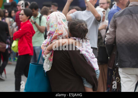 London,UK. 2nd August 2014. A mother carries a child during  the Eid festival in Trafalgar Square London to mark - Stock Photo