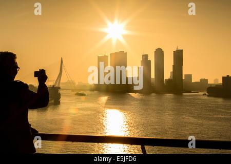 Netherlands, Rotterdam, Kop van Zuid District highrise buildings. Erasmus bridge. Sunrise. Man takes picture - Stock Photo