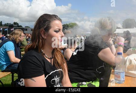 A young woman exhaling her vapouriser at Vapefest 2014. e cigarette smoking vaping - Stock Photo