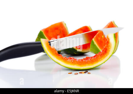 Kitchen knife stuck in a piece of watermelon isolated on white Background - Stock Photo